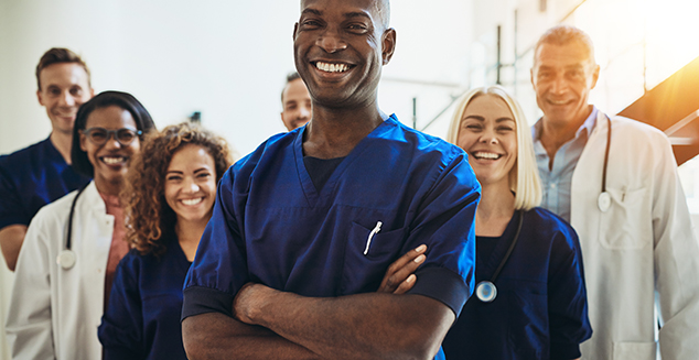 Young African male doctor smiling while standing in a hospital corridor with a diverse group of staff in the background