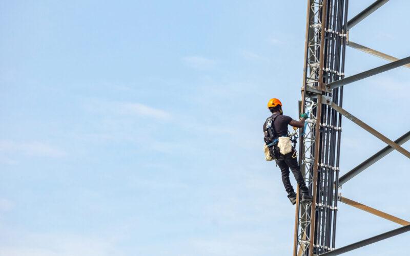 Communication maintenance. Technician climbing on telecom tower antenna against blue sky background, copy space.