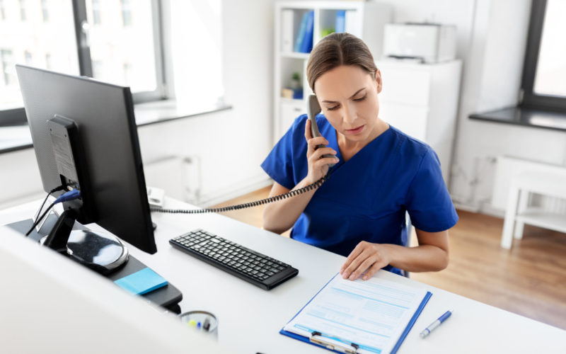 medicine, technology and healthcare concept - female doctor or nurse with computer and clipboard calling on phone at hospital