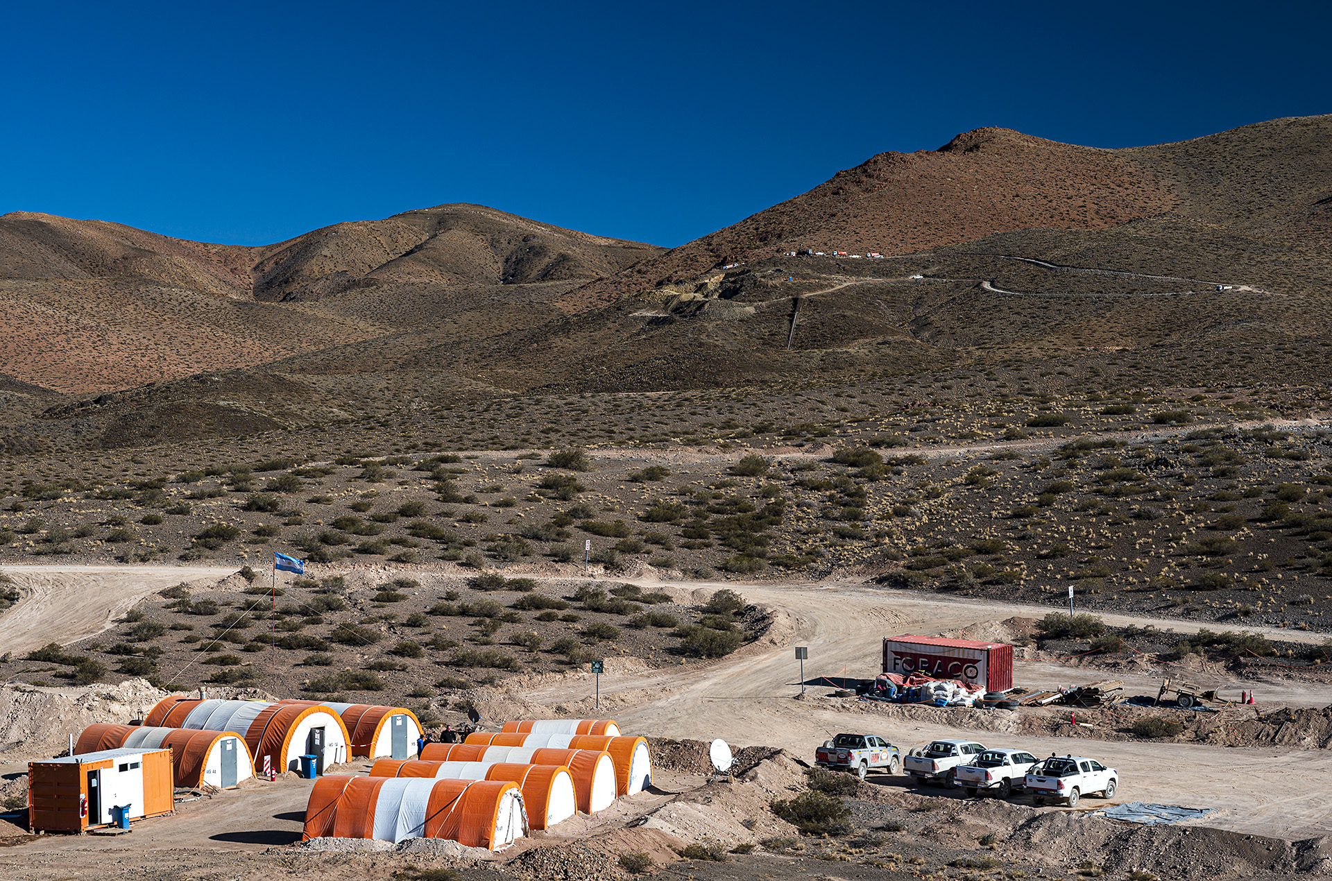Figure 1 - San Francisco Project area: temporary company camp in foreground and drill rigs at the San Francisco del Los Andes breccia pipe in background. The project is located in an arid, sparsely populated area at an elevation of ~2600m. The camp is located 20km by unsealed road to the nearest public road and the state power grid.