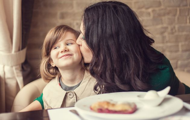 Woman kissing child with meal