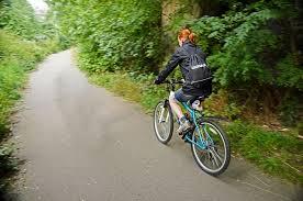 Woman mountain biking in forest on road