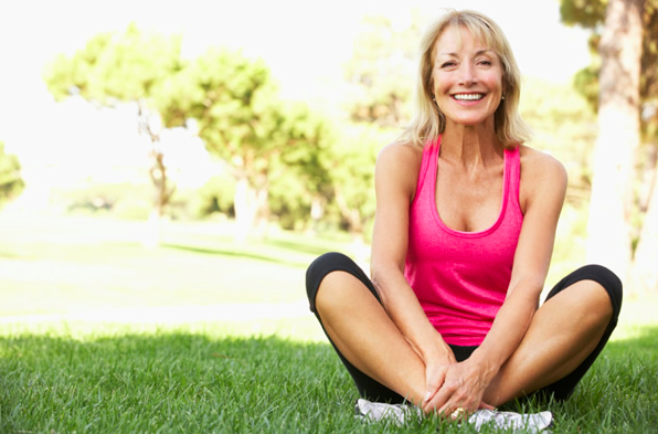 smiling woman sitting on grass