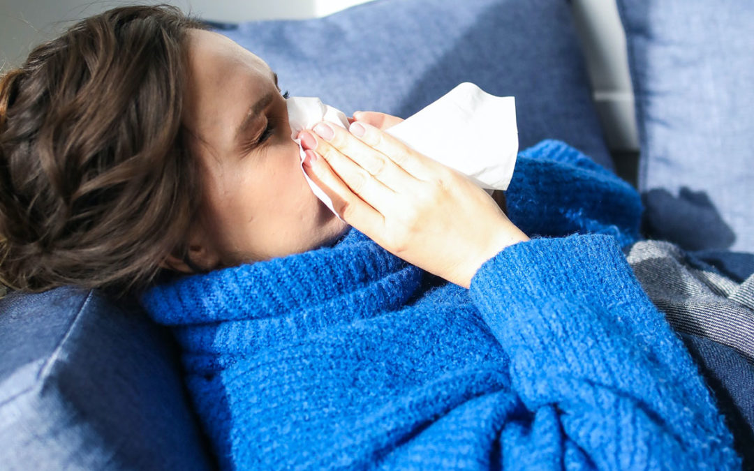 Ill woman in blue sweater blowing nose while laying on the sofa.