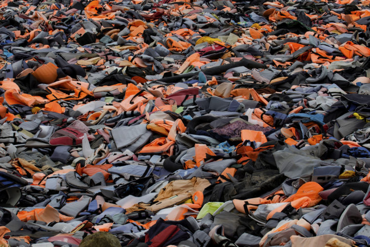 "LESVOS, GREECE (EU) 06-04-2017: The ""Lifejacket Graveyard,"" a dumping ground for thousands of discarded life jackets and rubber rafts used by refugees and their smugglers to get to Lesvos, Greece, has become a symbol of the thousands of refugees who have sought asylum in Greece (EU), including many who drowned."