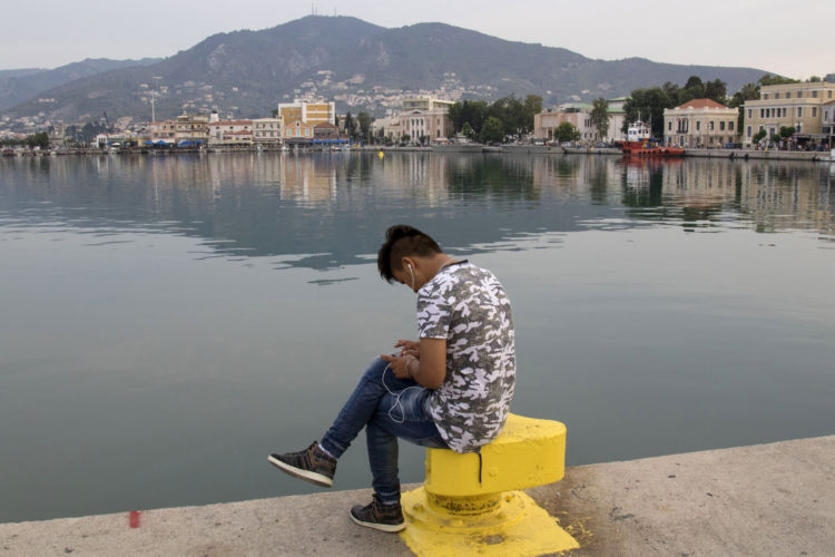 LESVOS, GREECE  06/03/2017: A young migrant checks messages on his phone while sitting by the harbor in Mytilene.  Lesvos is one of the Greek islands most burdened by the refugee crisis; about 8,700 of the 60,000 migrants living in Greek camps are housed here. In recent months, migrants have held protests here over poor living conditions at state-run camps and delays in the processing of their asylum applications, and have sparked clashes with local members of the far-right, whose tolerance of the growing refugee population has worn thin.