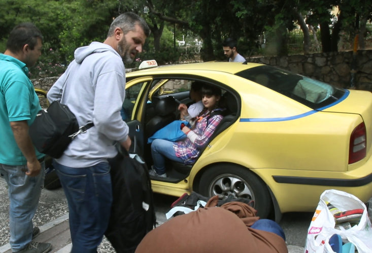 ATHENS, GREECE (EU) 05-29-2017: Hosem Al Rahmoun loads his family and their belongings into an awaiting taxi. Today his family is moving into their new apartment after living in a refugee squat in an abandoned school building in Athens for the past few months. They are being sponsored by two sisters in New York who raised money for them through HumanWire's Tent-to-Home Project.