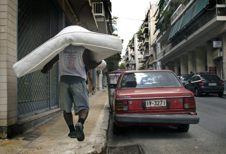 ATHENS, GREECE (EU) 05-30-2017 : A man carries a mattress for a refugee family relocated in Athens.