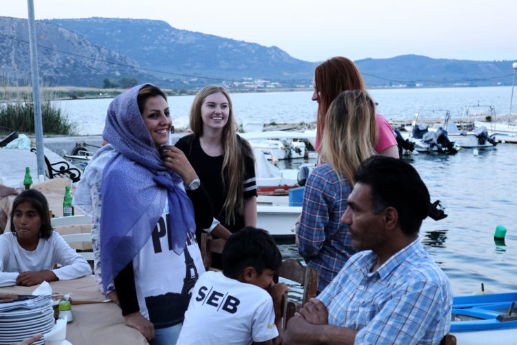 "LESVOS, GREECE (EU)  06/03/2017: Refugees and volunteers from the nearby Moria Refugee camp socialize before dinner at ""Home for All,"" the Mytileni restaurant that serves dinner each night to refugees for free on the island of Lesvos. A gathering point for donations of goods and emotional support, Home is run by restaurant owners Nikos and Katerina Katsouris, and has become an important gathering point for donations of goods and emotional support, for refugees."