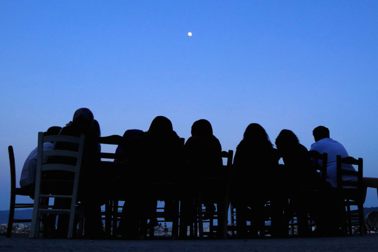 """LESVOS, GREECE (EU)  06/03/2017: Refugees and volunteers from the nearby Moria Refugee camp sit down for dinner in the moonlight dinner at """"Home for All,"""" the Mytileni restaurant that serves dinner each night to refugees for free.  A harbor-side gathering point for donations of goods and emotional support,  Run by restaurant owners Nikos and Katerina Katsouris, Home has become a gathering point for donations of goods and emotional support, for refugees."""