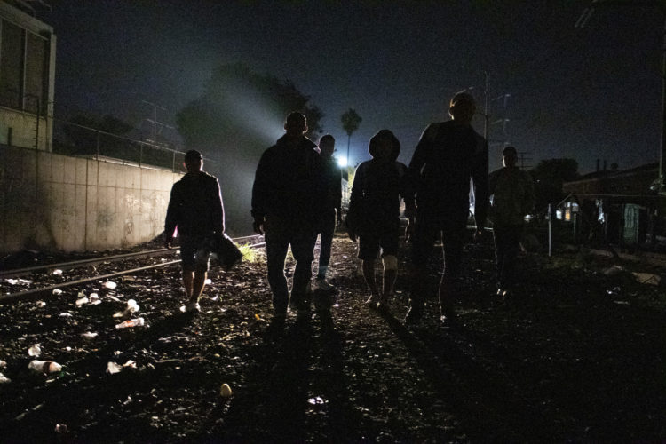 GUADALAJARA, MEXICO  07-13-2017: A group of Honduran migrants walk along the railroad tracks in Guadalajara, roughly the midway between Central American and the U.S. looking for a position to jump onto the trains, known as The Beast. According to the Migration Policy Institute (MPI), a half a million Central American immigrants ride atop La Bestia during their long and perilous journey through Mexico to the U.S. The migrants often must latch onto the moving freights, which run along multiple lines, carry products north for export, and must ride atop the moving trains, facing physical dangers that range from amputation to death if they fall or are pushed. Beyond the dangers of the trains themselves, Central American migrants are subject to extortion and violence at the hands of the gangs and organized-crime groups that control the routes north.