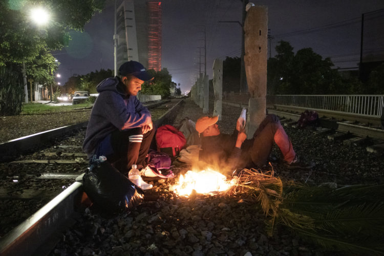 GUADALAJARA, MEXICO   07/13/2017  A group of Honduran men make campfire along the railroad tracks in Guadalajara, where wild dogs and gang members lurk in the shadows, as they continue on the journey to the U.S. border. After leaving the nearby FM4 shelter, the men walked along the railroad tracks to a position where they wait to jump on board La Bestia, the moving freight train known as The Beast. 