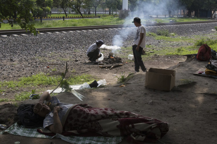 GUADALAJARA, MEXICO  07/14/2017: A group of Honduran migrants make camp along the railroad tracks in Guadalajara, roughly the midway between Central American and the U.S., along the route of Mexican freight trains that are utilized by U.S.- bound migrants to more quickly traverse the length of Mexico, also known as La Bestia and El tren de los desconocidos. This mode of travel is extremely dangerous and illegal.  
