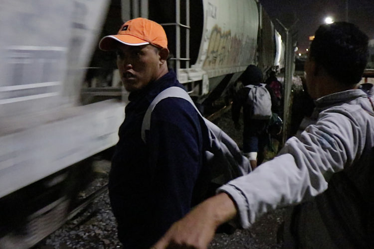 GUADALAJARA, MEXICO   07/13/2017  A group of Honduran men take positions along the railroad tracks preparing to jump on board the fast moving freight train known as The Beast. The men wait for a slow down and then run on the rocky gravel alongside the moving train looking for a boxcar that has a ladder to grab ahold of and hoist themselves to board the train. La Bestia (the Beast) is utilized by U.S. bound migrants to more quickly, and at no cost, to traverse the length of Mexico. This mode of travel is extremely dangerous and illegal.  