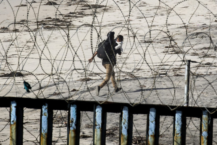 TIJUANA, MEXICO  03-13-2019: A 22-year old Honduran man carries his young daughter in his arms as he runs down the beach on the U.S. side of the border wall, after he squeezed through pillars and fencing at La Playa in Tijuana. The man dramatically sprinted down the beach towards San Diego. Remarkably, he was not captured, and is currently living with family elsewhere in the U.S.