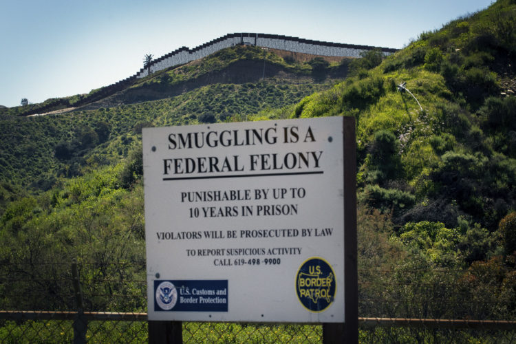 SAN YSIDRO, CA  03/12/2019: A warning sign is posted in International Park in San Ysidro warning that smuggling is a federal offense, as the border wall between Tijuana, Mexico and San Ysidro can be seen in the distance. The U.S.-Mexico border is 1,933 miles long, stretching from the Pacific Ocean to the Gulf of Mexico, roughly 700 of those miles have fencing currently in place.In July 2019, the Supreme Court gave President Trump a victory in his fight for a wall along the Mexican border by allowing the administration to begin using $2.5 billion in Pentagon money for the constructionIn the run-up to his election victory, Mr Trump promised to build a wall along the border's entire 2,000-mile length.He later clarified that it would only cover half of that - with nature, such as mountains and rivers, helping to take care of the rest. But, since Mr Trump entered the White House, although some of the already existing barriers have been replaced, work on extending the current barrier has only just begun