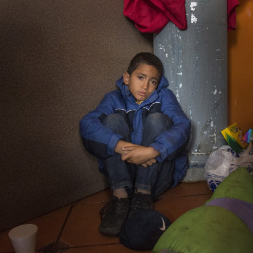 TIJUANA, MEXICO  03-09-2019: Patric Murillo, 12, of Honduras, sits on the floor of a cafe in Tijuana that offers free food to migrants. He just arrived with his mother and two brothers after traveling for two months in a migrant caravan from Honduras. The Border Angels volunteers then brought them clean clothes, hygiene products and directions to the nearby shelter.