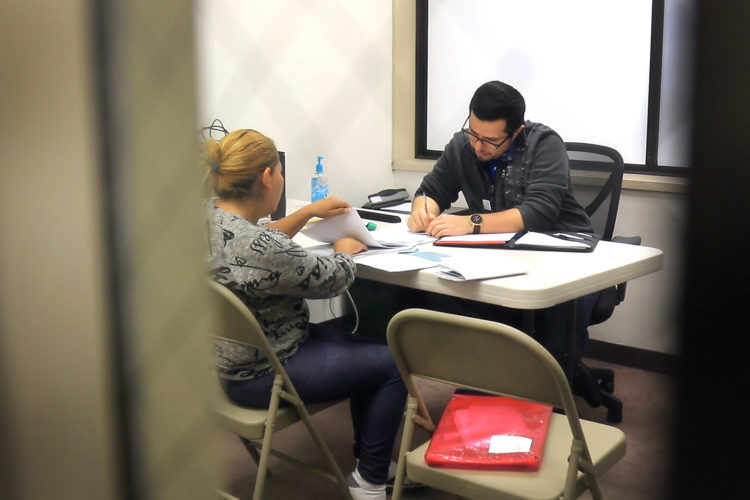 """SAN DIEGO, CA  03/11/2019: Luis Gonzalez, an attorney who assists asylum seekers near the U.S.-Mexico border, meets with a client from Central America seeking asylum in the U.S. inside an office in the temporary emergency shelter in San Diego. Gonzalez is the """"Border Fellow"""" for the Hebrew Immigrant Aid Society (HIAS), part of their response to the crisis at the southern U.S. border. He has been working at Jewish Family Services, a HIAS affiliate, since the fall of 2018. He meets daily with clients either in the ICE detention center, temporary shelter, or in his office, and assists migrants navigate the asylum process.(her name is Jessica Vasquez Ramos)"""