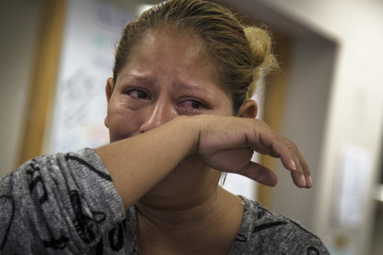 SAN DIEGO, CA  03/11/2019: A woman (unidentified) from Central America wipes away some tears while speaking with her attorney Luis Gonzalez, a HIAS Border Fellow who took on her case pro-bono. The single mother arrived in Tijuana with a migrant caravan in late February 2019, after a two month journey. She is seeking asylum in the U.S. for herself and children, after they were victims of gang violence and sexual assault at home.(her name is Jessica Vasquez Ramos)