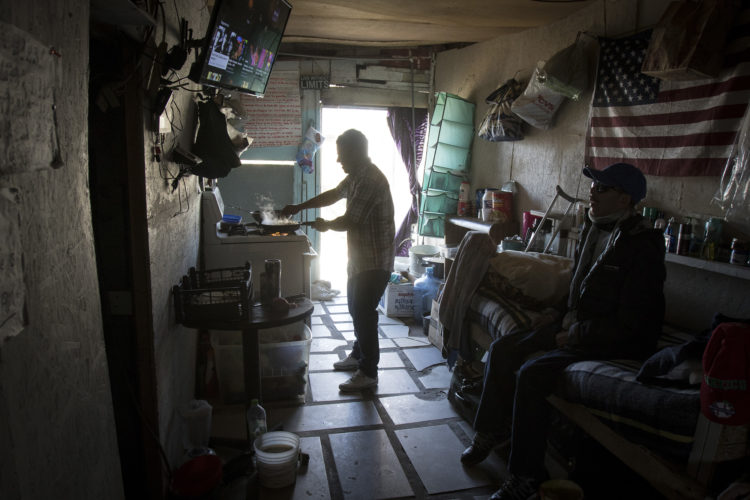 TIJUANA, MEXICO  03-12-2019: Two migrants cook food  on open stove and watch TV in the midday light in a small boarding room in La Playa, near the beach and border wall in Tijuana.