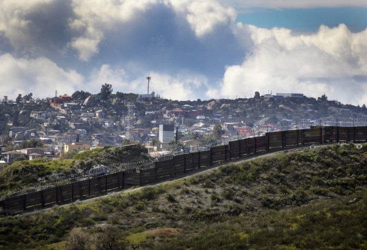 TECATE, CA  03/12/2019: The city of Tecate, Mexico can be seen beyond the border wall. Tecate is a city split between the U.S. and Mexico of the same name. In June 2019, U.S. Customs and Border Protection (CBP) announced they would begin construction of approximately 15 miles of new border wall in place of dilapidated and outdated designs, including the construction of 30-foot tall steel bollards and technology improvements.