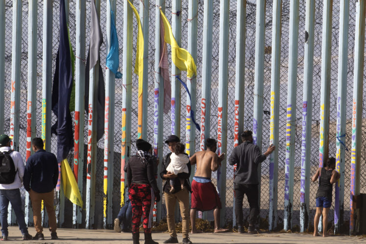 SAN DIEGO, CA- TIJUANA, MX   03-13-2019 U.S.-MEXICO BORDER WALL HONDURAN MIGRANTS BREAK THROUGH BORDER WALL:   At center, a 22-year old Honduran man says final words to his wife before he squeezed through the pillars in Tijuana yesterday  carrying his young child in his arms while the Customs & Border Patrol (CBP) was not on watch, and then sprinted down the beach heading towards San Diego. Shortly after, a teenage boy followed him, and then another father and young girl also went through the fence. CBP was late in spotting them, and a single agent ran after them lagging far behind, as people on the TJ side jeered. They all disappeared into the distance and did not appear to be captured, but this was not confirmed.-photo by Thomas E. Franklin