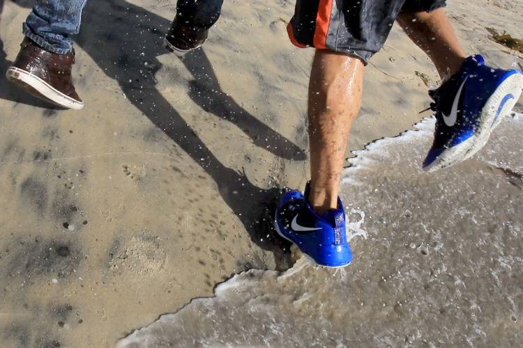TIJUANA, MEXICO  03-14-2019: Two migrants run in the surf after they squeezed through an opening in the border fence on the beach running past a CBP agent and ran north along the beach into the United States. They were later captured by United CBP agents, who said they arrested about 52 migrants, including 23 men, between the ages of 18 to 53, 12 women aged 21 to 50, and 17 minors between the ages of 1 and 14 years old. They were mostly from Honduras and came to Tijuana in a caravan. As they broke through the fence and ran down the beach, some dropped clothes and shoes from the backpacks, as some people on the Mexico side cheered them on.