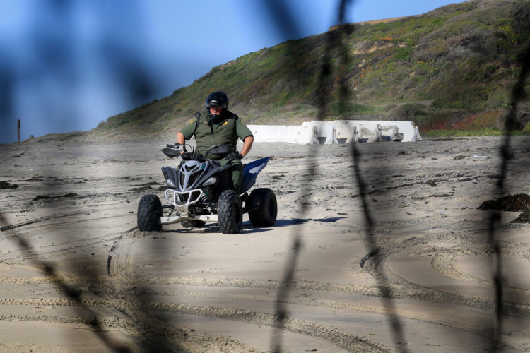 SAN DIEGO, CA- TIJUANA, MX   03-14-2019 U.S.-MEXICO BORDER WALL HONDURAN MIGRANTS BREAK THROUGH BORDER WALL:   A Custom Border Patrol Agent watches the wall on a 4x4 after a group of roughly 20-30 migrants squeezed through an opening in the border fence on the beach on La Playa Tijuana today, running past border patrol heading towards SanDiego.-photo by Thomas E. Franklin