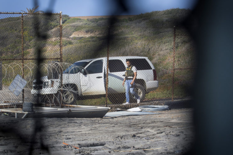 TIJUANA, MX   03/13/2019: A CBP agent gets into an SUV on the U.S. side of the border fence, after a group of migrants pushed through an opening in the border fence on the beach running past a CBP agent and ran north along the beach into the United States.