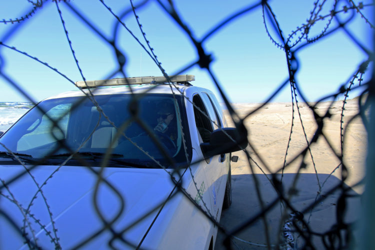 TIJUANA, MX   03/14/2019: A Custom Border Patrol Agent parks his SUV wedged up against the border fence to close the opening created by migrants after a group of migrants pushed through an opening in the border fence on the beach running past a CBP agent and ran north along the beach into the United States. They were later captured by United CBP agents, who said they arrested about 52 migrants, including 23 men, between the ages of 18 to 53, 12 women aged 21 to 50, and 17 minors between the ages of 1 and 14 years old. They were mostly from Honduras and came to Tijuana in a caravan. As they broke through the fence and ran down the beach, some dropped clothes and shoes from the backpacks, as some people on the Mexico side cheered them on.
