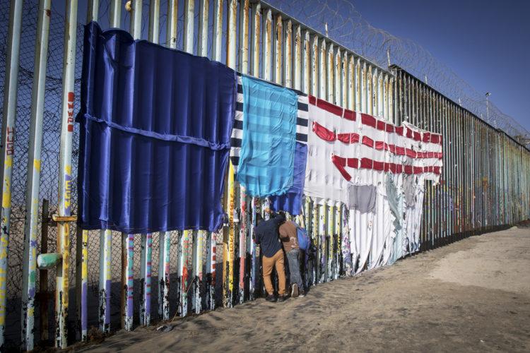 TIJUANA, MEXICO  03/13/2019 Two people peer through the border wall looking towards the U.S. side on the beach in La Playa, Tijuana.