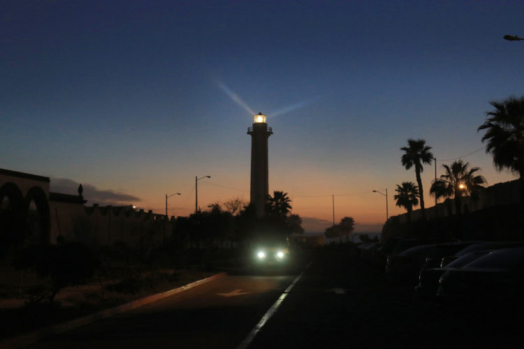 TIJUANA, MEXICO  03/13/2019: Tijuana's lighthouse, or faro, is where the northwestern nook of Latin America meets the southwestern tip of the U.S. at the Pacific Ocean. The coastal esplanade south of the fence boundary is a beachy hangout for activists, artists, and tourists snapping selfies. It's also the site where desperate stranded deportees gather and gaze through the steel fence looking at the U.S., so close but yet so far away. The Mexico-side of the border fence has become a kind of politically charged art installation, featuring images, poems, and slogans, most condemning President Trump and U.S. immigration policy. The U.S. side is controlled by CBP and is off-limits to the public.