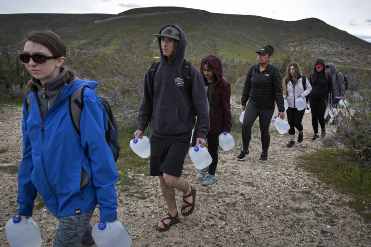 "IMPERIAL COUNTY, CA 03/10/2019:  Border Angels led a team of volunteers, including a group of students from University of Utah, and carried gallons of water into the Imperial Valley in southeastern Southern California near the Mexico border and hid the plastic bottles scattered along trails that undocumented migrants often take after crossing into the California.  Along the trails, discarded items such as makeshift foot coverings migrants use to avoid leaving footprints could be seen as well as other discarded clothes and remnants of campfires. The conditions here are extreme, often were windy and cold at night, and extremely ward during the daytime. Border Angels is a nonprofit that has been leading humanitarian efforts such as ""water drops"" in the desert for migrants for over 20-years. In 2019, two border aid volunteers were sentenced to 15 months of probation, must pay fines for dropping off water and food intended for migrants crossing through a protected desert area in southern Arizona."