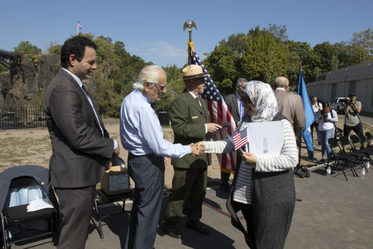 PATERSON, NJ  10-02-2019 NATURALIZATION CEREMONY AT GREAT FALLS:  After receiving her Naturalization Certificate, Rachida El Ghyati of Paterson shakes hands with Congressman Bill Pascrell, Jr. and Mayor of Paterson Andre Sayegh. She is from Morocco. The Paterson Great Falls National Historical Park (NPS), in partnership with U.S. Citizenship and Immigration Services (USCIS), held a naturalization ceremony in the park's new amphitheater where 40 new citizens, mostly residents of Paterson, took the Oath of Allegiance to the United States.