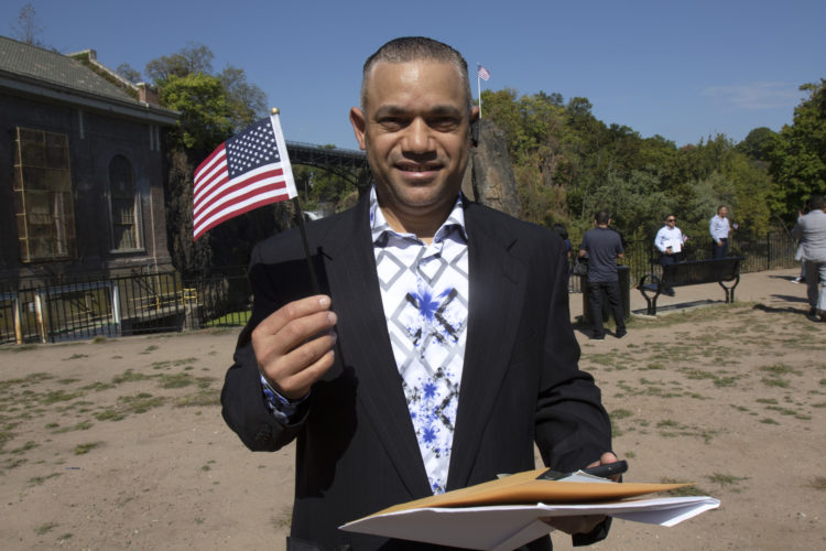 PATERSON, NJ  10-02-2019 NATURALIZATION CEREMONY AT GREAT FALLS:  Elvin Molina DeLeon waves the U.S, flag after taking the Oath of Allegiance to the United States. He is from the Dominican Republic. The Paterson Great Falls National Historical Park (NPS), in partnership with U.S. Citizenship and Immigration Services (USCIS), held a naturalization ceremony in the park's new amphitheater where 40 new citizens, mostly residents of Paterson, took the Oath of Allegiance to the United States.