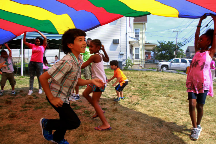 ELIZABETH, NJ  07-26-2016: Mohammed (last name withheld), a 9-year old Syrian boy, runs under a parachute while playing outdoors with other children at the Gateway Family YMCA, Elizabeth Branch Summer Camp. Syrian children recently relocated to New Jersey with their families from war-torn Syria, attended a fun-filled summer camp thanks to sponsorship of two Jewish synagogues,  Bnai Keshet in Montclair and Temple Bnai Abraham in Livingston. At the camp, 16 refugee children ages 5-14 had the opportunity to play games, interact with other children and staff, and use the camp as an opportunity to improve their English and assimilate.