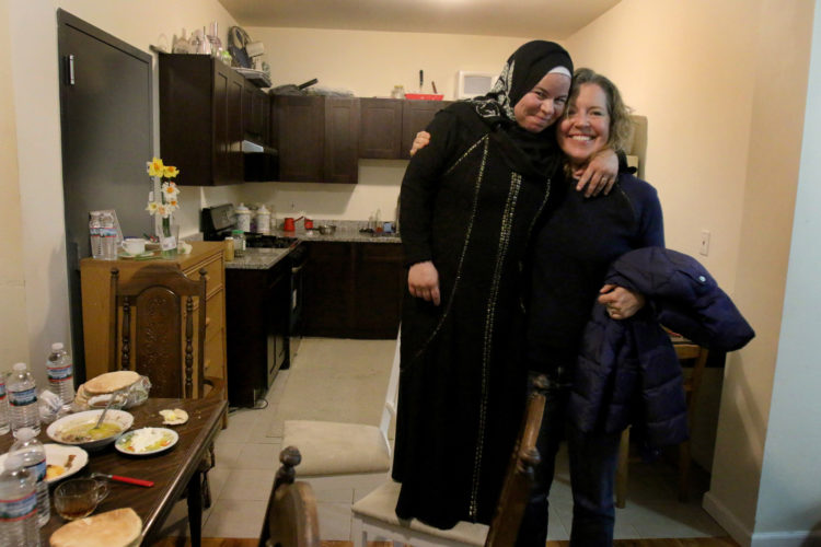 "ELIZABETH, NJ   04/03/2016   SYRIAN REFUGEE FAMILIES RESETTLED IN ELIZABETH:   Maryam Al Radi jokingly stands on a chair because she is short, as she hugs her new friend Kate McCaffrey  from Bnai Keshet Synagogue. Bnai Keshet has ""adopted"" the AL Radi's, providing friendship and assistance in helping the family get acclimated to their new life in the US."