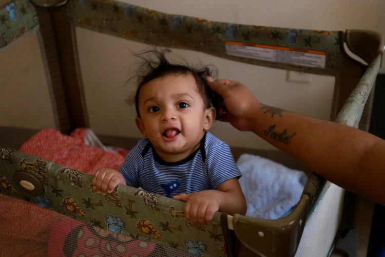 NEWARK, NJ  07-19-2018: Kasandra Serrano, 21, plays with her 9-month old son Ismael in the apartment complex where she is living with her mother and sisters. Serrano's fiancé Daniel Castro, 28, was taken into custody by Newark Police in June 2018 and turned over to ICE despite Newark's Sanctuary City policy. Castro, who is undocumented but has no criminal record and did not commit any offense the evening of his arrest, was falsely arrested, and Newark Police admit they made a mistake in violating the city's own Sanctuary City policy. On the night of his arrest, Castro was returning from shopping for baby formula when he was stopped by police and reluctantly gave his name when they arrested him for an outstanding ICE warrant from many years ago for which he said he was never notified. After many months of being held at the Elizabeth Detention Center (ICE) he was deported to his native Nicaragua where he currently awaiting a status hearing in New Jersey. The couple has a 9-month old baby boy, Ismael, and since Danny's arrest Serrano has been living with her mother, sisters, and their young children in a small apartment in Newark, and says she cannot support herself and the baby without government and family assistance.