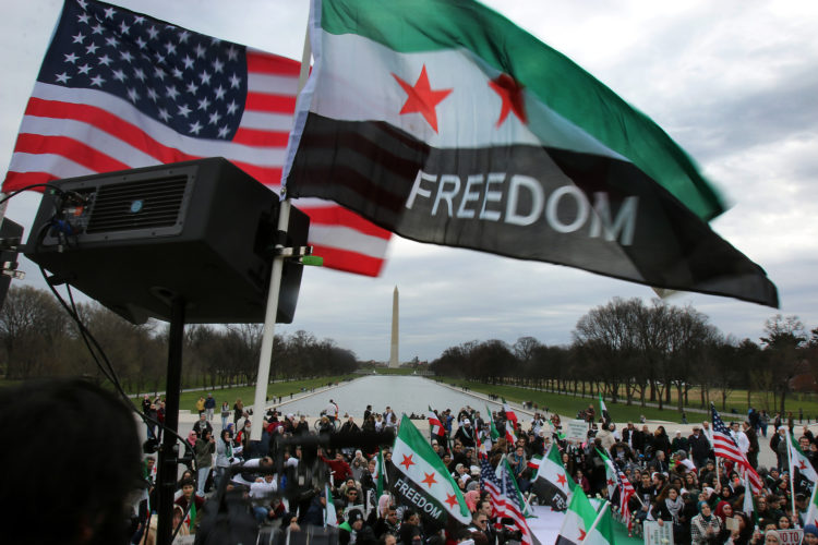"WASHINGTON D.C.  03/20/2016: Hundreds take part in the ""March for Syrian Freedom"" rally in Washington DC on the National Mall, marking the 5th Anniversary of the Syrian Revolution. Along with the flags of the U.S. the protesters carried Syrian Revolution flags, which are different that the Syrian national flag.  Five years after it began, Syria's civil war is among the worst humanitarian crisis of our time. The civil unrest has killed more than 220,000 of its citizens, and it has been estimated that over 11 million people have been forced to leave their homes. Bombings have destroyed cities, human rights violations are widespread, and basic human necessities like food, housing, and medical care are sparse. Roughly half of Syria's population has fled to either neighboring countries or to Europe, many risking their lives in hopes of finding acceptance and opportunity abroad, while hundreds of thousands remain stranded in refugee camps across the Middle East, Europe, and the Mediterranean region prompting rights groups to accuse the international community of failing Syria."