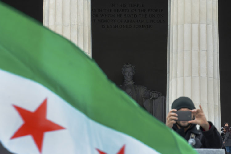 "PATERSON, NJ   03/20/2016: Mohamed Khairullah takes snaps a photo during the ""March for Syrian Freedom"" rally under the watchful eye of Abe Lincoln the at Lincoln Memorial. Khairullah, the mayor of Prospect Park, NJ and a refugee from Syria, escorted a group from Passaic County to participate in the rally commemorating the 5th anniversary of when the conflict began as an anti-government uprising with protesters taking to the streets on March 15, 2011, brings  attention to the global humanitarian crisis and raise money to aid Syrian refugees worldwide. The program included an interfaith conference at the Lincoln memorial, followed by a march to the White House."