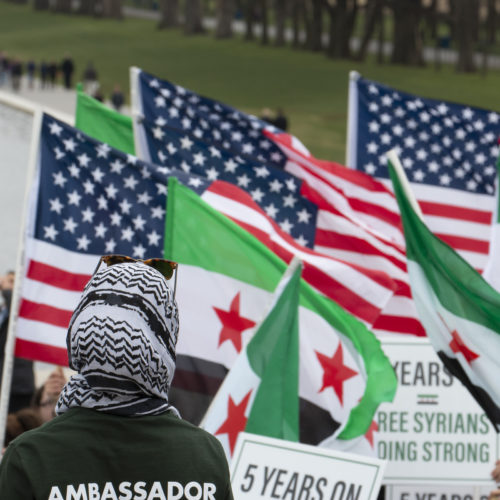 "WASHINGTON D.C.  03/20/2016: A woman wearing a head scarf watches the ""March for Syrian Freedom"" rally in Washington DC marking the 5th Anniversary of the Syrian Revolution. Along with the flags of the U.S. the protesters carried Syrian Revolution flags, which is different that the Syrian national flag.  Five years after it began, Syria's civil war is among the worst humanitarian crisis of our time. The civil unrest has killed more than 220,000 of its citizens, and it has been estimated that over 11 million people have been forced to leave their homes. Bombings have destroyed cities, human rights violations are widespread, and basic human necessities like food, housing, and medical care are sparse. Roughly half of Syria's population has fled to either neighboring countries or to Europe, many risking their lives in hopes of finding acceptance and opportunity abroad, while hundreds of thousands remain stranded in refugee camps across the Middle East, Europe, and the Mediterranean region prompting rights groups to accuse the international community of failing Syria."