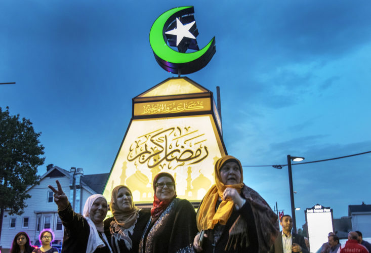 """PATERSON, NJ  05-04-19: A group of Muslim women pose for Instagram photos with the giant fanous, or lantern, illuminated at the South Paterson Park on Main Street to usher in the holy month of Ramadan. After a ceremony led by Andre Sayegh, the city's first Arab-American mayor, people gathered to have their photo taken. 6th Ward Paterson Councilman Al Abdellaziz, who helped start the tradition four years ago, said, """"We want this to become a destination, """"it's like the Muslim Rockefeller Center Christmas tree."""""""