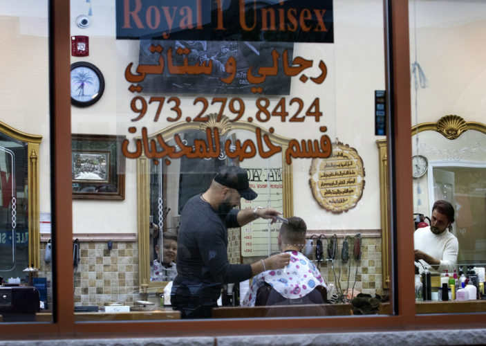 SOUTH PATERSON, NJ  05-04-19: Barbers cut hair at the Royal 1 Salon on Main Street in South Paterson, a bustling neighborhood in Passaic County where many of the stores and shops cater to Arab and Turks, evidenced by the signs in English and Arabic.