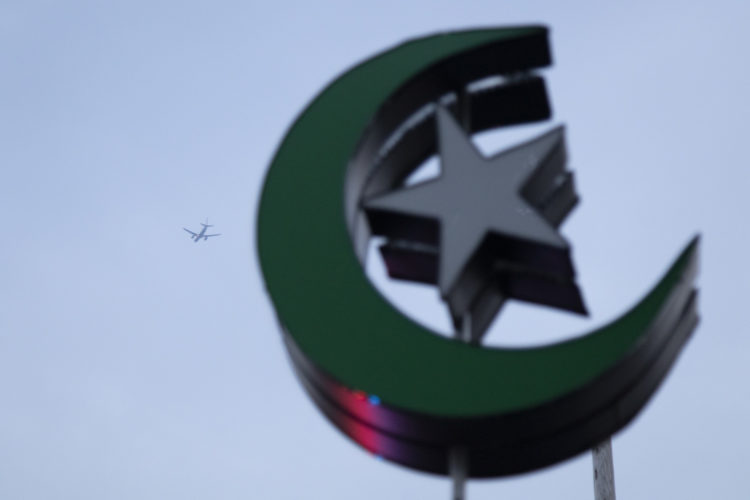 05-04-19 PATERSON, NJ:  An airplane flies over  the crescent moon and star, symbols of Islam, attached to the top of the lantern in South Paterson Park.