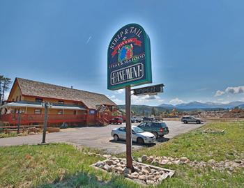 Basement restaurant exterior. Sign text: Strip & Tail, Crab & Ale, Steak & Seafood, Basement.
