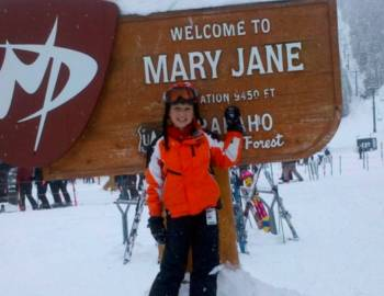Woman posing at Mary Jane sign. Text: Welcome to Mary Jane.