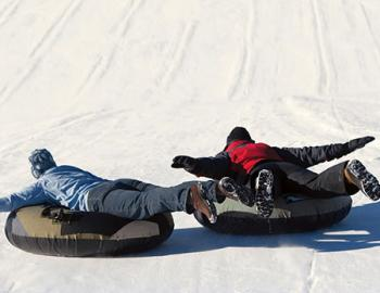 Adults laying on snowtubes.