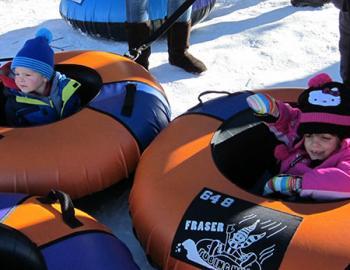 Little kids in snow inner tubes.