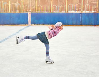 Young woman skating on one leg.