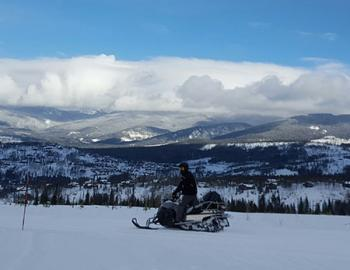Snowmobiler on the trail overlooking the mountains.